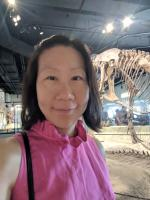 Wei Le  - A woman with black hair in a pink blouse smiles in front of a dinosaur skeleton.